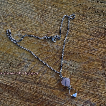 Rose Quartz Heart Shaped Pendant Necklace Small size with a small stainless steel heart on the bottom .